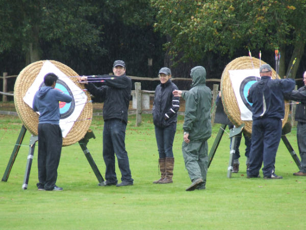 Archers pulling out arrows from targets.